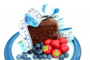 Photo showing a tape measure with chocolate cake, strawberries and blueberries. The cake and fresh fruit have been pictured with a tape measure as a concept image for healthy eating, dieting, calorie counting and being overweight.